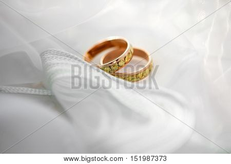 Engagement wedding rings of the bride and groom on a background of delicate white fabric wedding veils. Wedding accessories for the newlyweds.