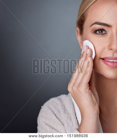 Beauty and nourished in middle age, lovely woman cleaning her skin on the cheek