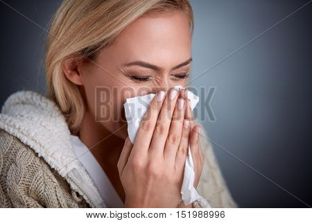 Cold woman holding handkerchieif blowing nose