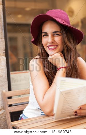 Woman long-haired brunette sitting in a coffee shop with a menu card in hand