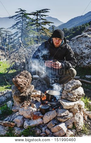Wanderer cooking on bonfire, seating with hot cup of coffee. Turkey, Lycian way, touristic trail.