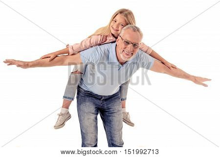 Portrait of cute little girl and her handsome grandpa looking at camera and smiling isolated on white. Girl is sitting pickaback and imitating flight