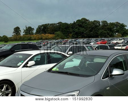 Cars parked in rows outside on grass in an overflow car park.