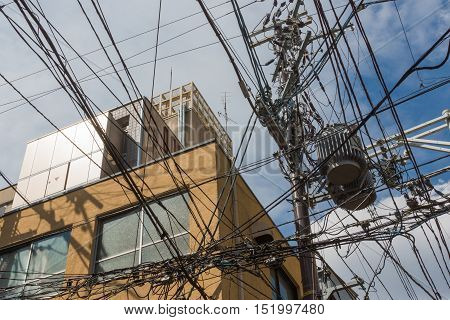 Kyoto Japan - September 16 2016: Power and communication cables create multiple cable nests as they are tangled under and above each other above the streets of Kyoto.