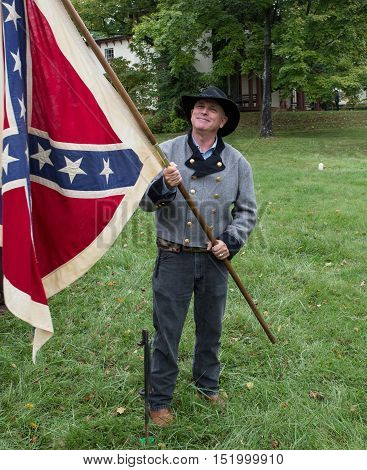 Warrenton, Virginia, USA-October 1, 2016: Man wearing historical costume holding Confederate flag at the Warrenton-Fauquier Heritage Day in Warrenton, Virginia.