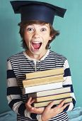 preteen handsome boy in graduation cap with book pile close up photo poster