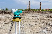 Surveyor engineer's equipment for measuring level on construction site. Surveyors ensure precise measurements before undertaking large construction projects. poster