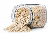 transparent glass jar with rolled oats isolated on white background. Glass jar with oatmeal flakes lying on side isolated on white background. Scattered oatmeal. Dry uncooked oat flakes oatmeal in glass transparent jar poster
