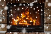 winter, christmas, warmth, fire and coziness concept - close up of burning fireplace at home with snow poster