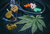 Medical marijuana products vs conventional pills, including cannabis leaf, dried bud, shatter piece, cbd caps and hash oil over black wood background poster