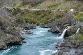 The Roaring Meg (Te Wai a Korokio) the turbulent stream that both drives this hydro electric power station and merges with the Kawarau River Central Otago south island of New Zealand poster
