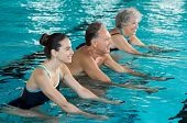 Happy smiling mature man and old woman cycling on a water bike in swimming pool. Happy and healthy senior people doing aqua aerobics on exercise bikes in a swimming pool. Fitness class training. poster