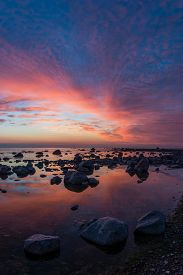 Colorful sunset sky and rocks in the sea - vertical image.