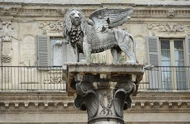 St. Mark's Lion symbol of the Republic of Venice on a white marble column at the Piazza delle Erbe in Verona Italy.