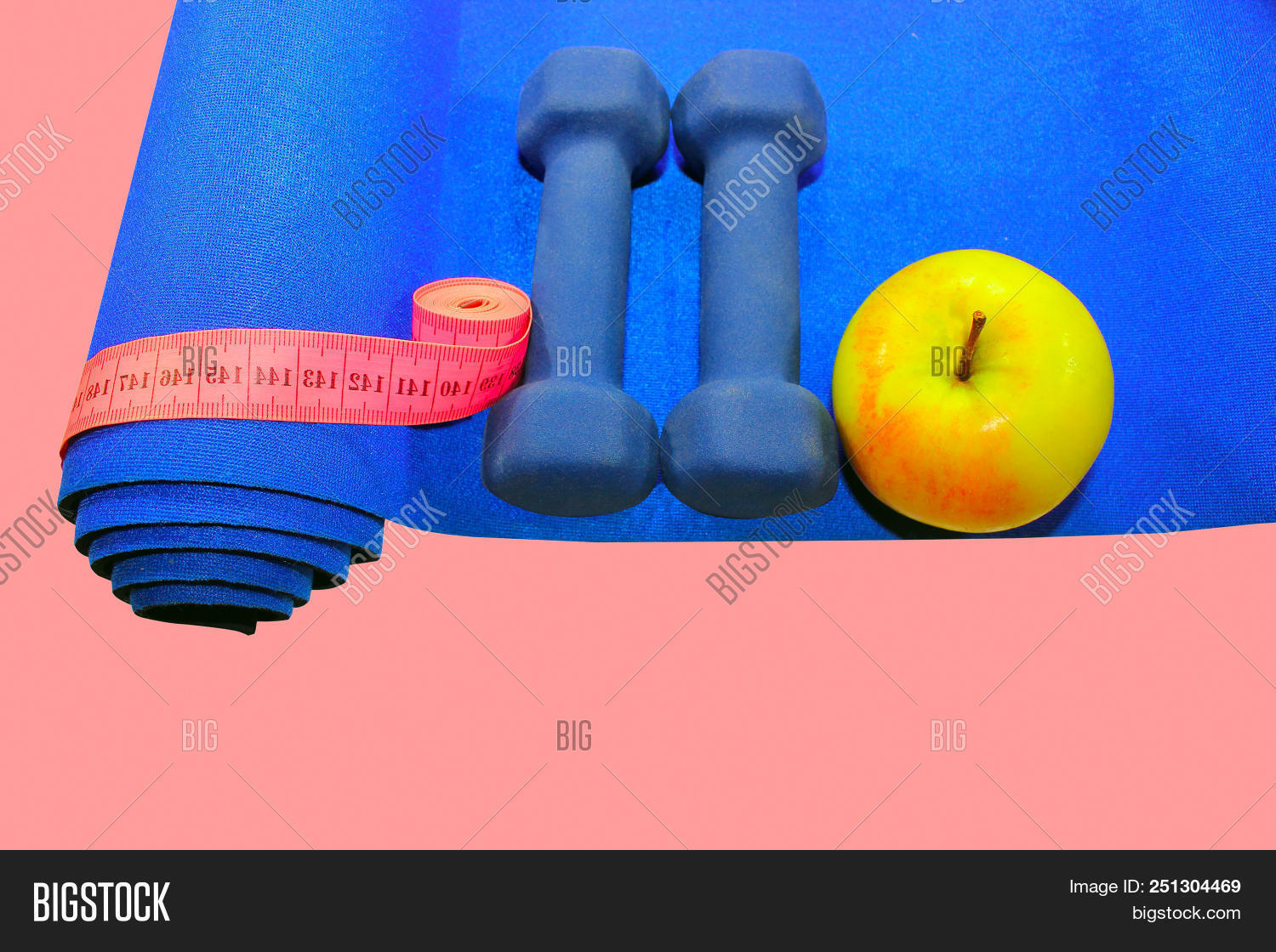 2d2a18c9d9e00 blue mat with dumbbells green apple drink measuring tape isolated on pink  background, concept of healthy lifestyle