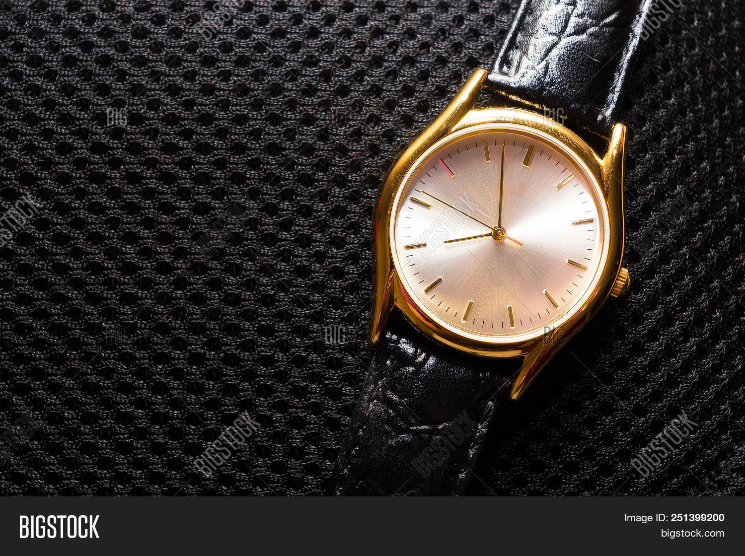 d60172c83 Gold metal watch. Black fabric background pattern. Clock hands. Black leather  strap. Time.