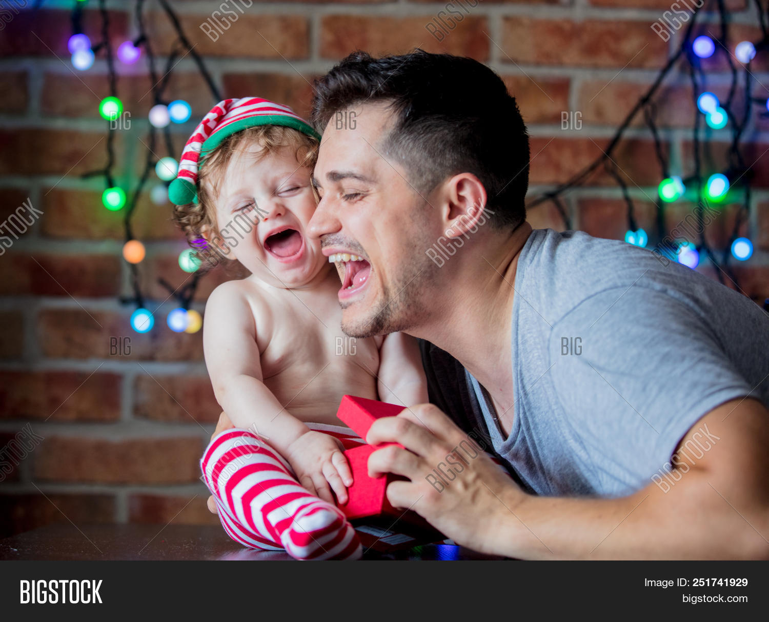 0bd69dd2df97b Beautiful little baby boy in elf hat and father with gift box and fairy  lights on background. Christmas time season image