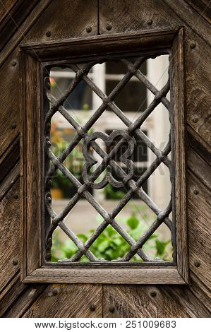 Closeup Of Small Window With Iron Bars In An Old Wooden Door Leading To A Garden.