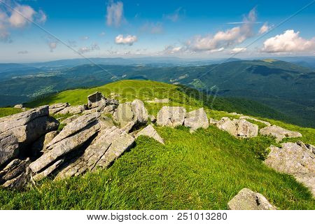 Boulders Down The Grassy Slope Of A Hill. Beautiful Sky Over The Distant Mountains. Stunning Summer