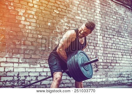 Athletic Man Working Out With A Barbell In Front Of Brick Wall. Strength And Motivation. Outdoor Wor