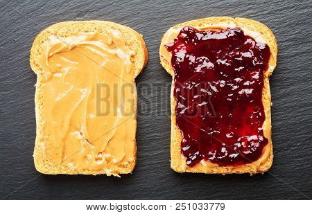 Sandwich With Peanut Butter And Jelly On Slate Background