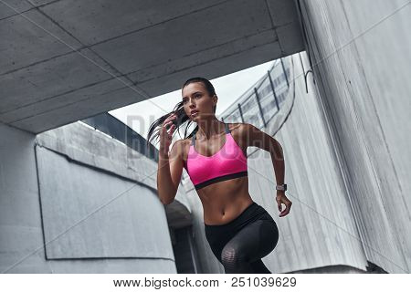 Towards A Healthier Lifestyle. Modern Young Woman In Sports Clothing Running While Exercising Outdoo