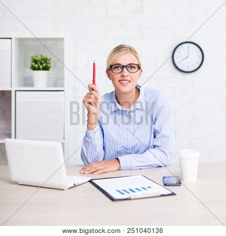 Idea Concept - Cheerful Business Woman Sitting In Office And Showing Idea Sign