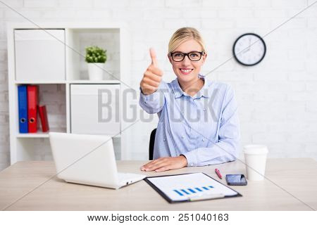 Cheerful Business Woman Sitting In Modern Office And Thumbs Up
