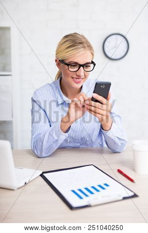 Portrait Of Business Woman Using Smart Phone In Office