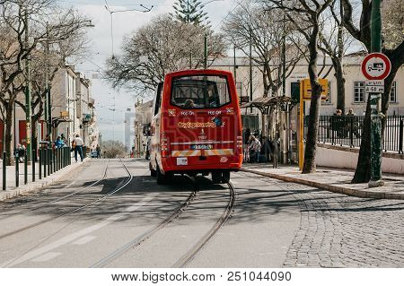 Portugal, Lisbon, 01 May 2018: A Traditional Red Tourist Bus Travels Along The City Street. Entertai