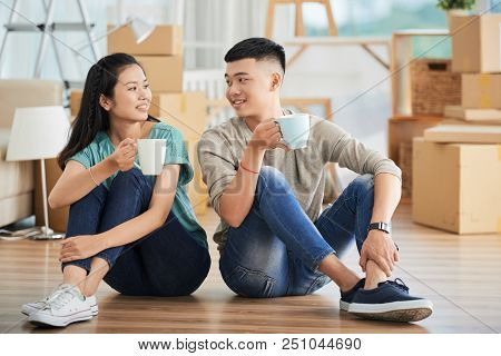Cheerful Young Asian Couple Sitting Together With Mugs Of Hot Beverage On Floor And Looking At Each