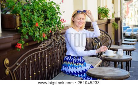 Woman winking face have drink cafe terrace outdoors. Girl drink tea with milk as aristocratic tradition. Mug of good tea with milk in morning gives me energy charge. Traditional tea with milk. poster