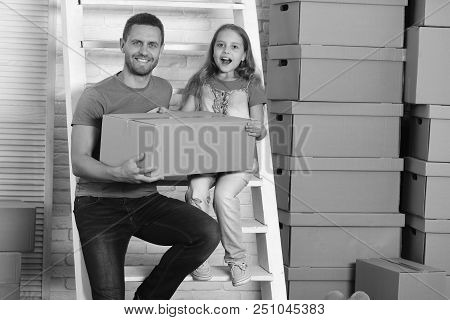 Daughter And Father Hold Boxes And Unpack Or Pack. Girl And Man With Smiling And Surprised Faces Wit