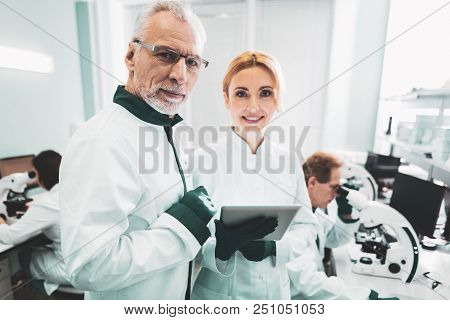 Working Process. Smiling Successful Scientists Feeling Satisfied While Enjoying Working Process In M