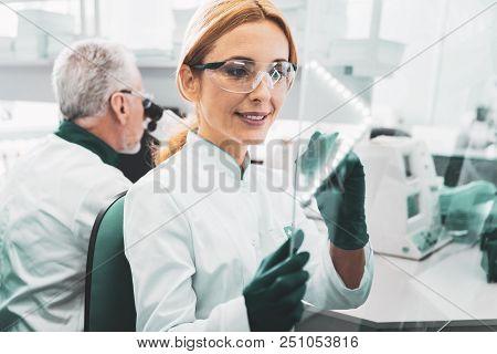 Molecular formula. Female promising chemist wearing glasses writing molecular formula on glass board poster