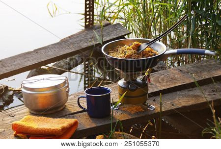 Camping Food Making. Pasta On Pan On Tourist Fire Stove. Camp Cooking On The Shore Of The Lake.