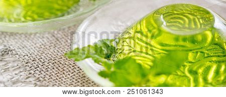 Green jelly with mint leaves in glass on wooden background. Juice with ice in gelatin. on a linen napkin on a white background. Long wide banner. poster
