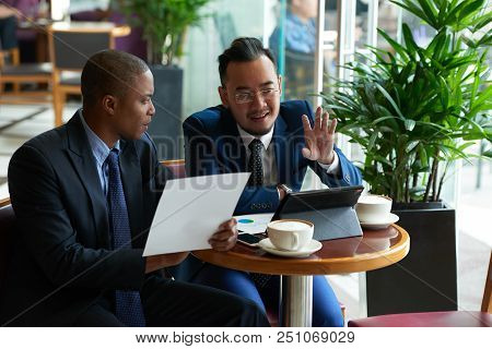 Cheerful Multi-ethnic Business People Discussing Ideas At Meeting In Cafe