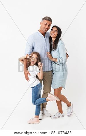 Portrait of a happy family father, mother, little daughter hugging isolated over gray background