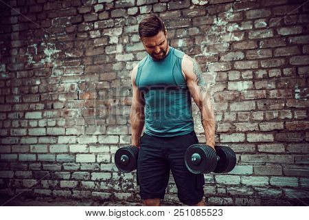 Athletic Man Working Out With A Dumbbell In Front Of Brick Wall. Strength And Motivation. Outdoor Wo