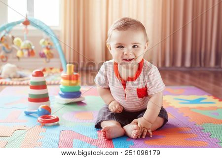 Portrait Of Cute Adorable Blond Caucasian Smiling Child Boy With Blue Eyes Sitting On Floor In Kids