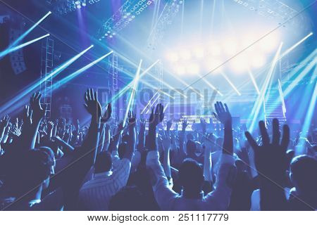 Young people with pleasure spending evening on the concert, crowd with raised up hands standing in blue lights, singing and enjoying music concept