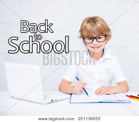 Back To School - Happy Little School Boy In Glasses Doing Homework With Modern Laptop