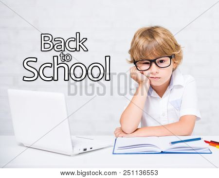 Back To School - Bored Little School Boy In Glasses Doing Homework At Home