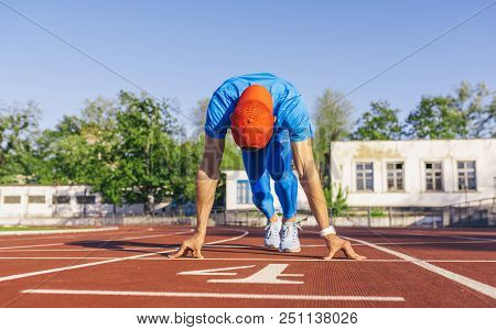 Sport, lifestyle and people concept. Sprinter athlete male at starting position ready to start a race. Man sprinter ready for sports exercise on racetrack in stadium. poster