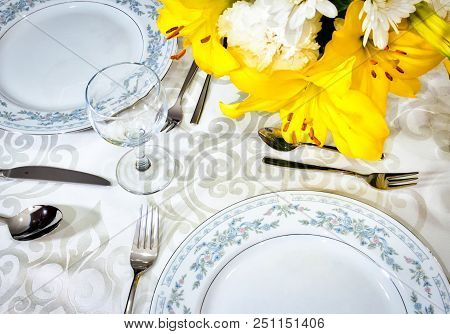 Elegant Dining Set For A Romantic Meal On A White Tablecloth In A Fancy Restaurant With Arranged Flo