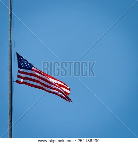 An American Flag Blowing In The Wind While Hanging From A Flagpole.