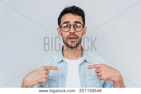 Closeup Portrait Of Handsome Bearded Young Man Points At Himself Being Puzzled To Be Chosen. Handsom