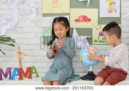 Cute Asian Boy And Girl Sitting And Playing With Globe And Toy House In Art Class