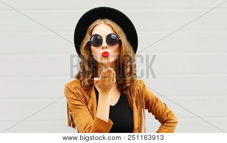 Pretty Woman Sends Air Sweet Kiss Wearing A Black Hat, Sunglasses And Brown Jacket Outdoors Over Urb